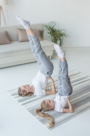 mother and daughter practicing yoga in Supported Shoulder Stand pose at home 스톡 콘텐츠 - 112015826