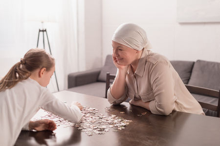 Cute little child with sick grandmother in kerchief playing with jigsaw puzzle together
