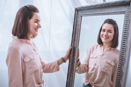 Beautiful smiling young woman standing near mirror and looking at reflection