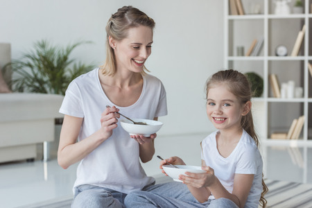 Mother and daughter eating cereal meal while sitting on floor 스톡 콘텐츠 - 112044905