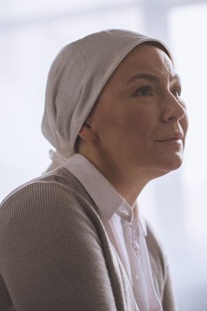 portrait of sick mature woman in kerchief looking away