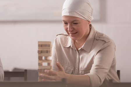 sick smiling mature woman in kerchief building tower from wooden blocks at home Stock Photo