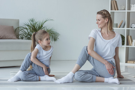 mother and daughter practicing yoga together in Marichi's pose