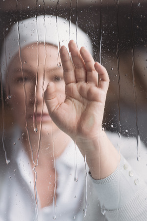 Close-up view of sick mature woman in kerchief touching window with raindrops