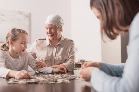 Happy family playing with jigsaw puzzle together, cancer concept Stock Photo