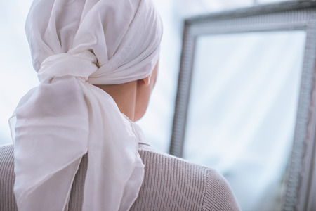 back view of sick woman in kerchief standing near mirror, cancer concept Stok Fotoğraf - 112016326