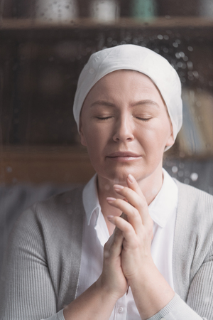 portrait of sick mature woman in kerchief praying with closed eyes Stok Fotoğraf
