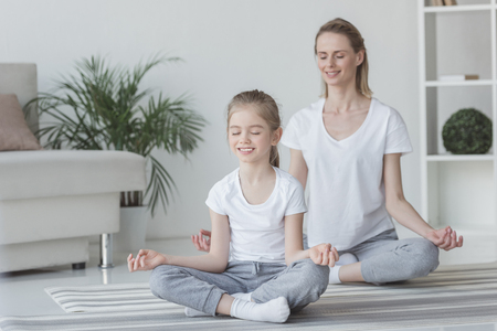 Smiling mother and daughter meditating in lotus pose at home
