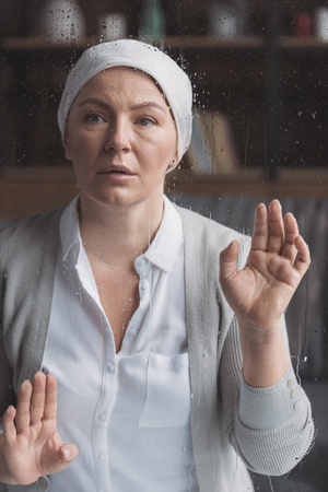 sick mature woman in kerchief looking at camera through glass with raindrops Stok Fotoğraf