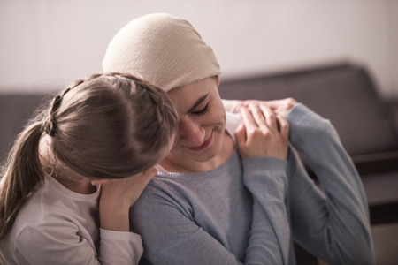 child hugging and supporting sick mother in kerchief Stok Fotoğraf