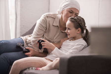 smiling grandmother and granddaughter playing with joysticks, cancer concept Banco de Imagens