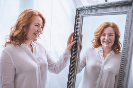 mooie lachende volwassen vrouw die in de buurt van de spiegel staat en naar reflectie kijkt Stockfoto