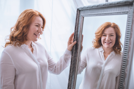 schöne lächelnde reife Frau, die in der Nähe des Spiegels steht und Reflexion betrachtet Standard-Bild