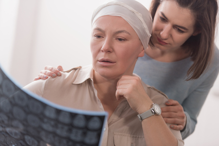 Woman supporting sick mature mother holding mri scan