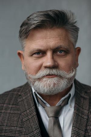 close-up portrait of stylish senior man with grey beard looking at camera