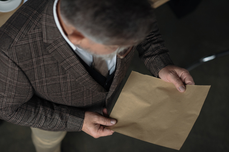 High angle view of senior man in tweed suit reading letter