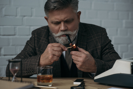 Serious senior writer smoking pipe at workplace