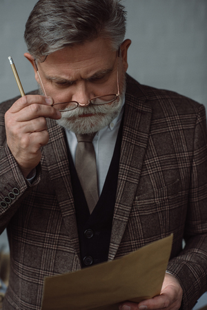 Thoughtful senior man with pencil and sheet of paper Imagens - 112089876