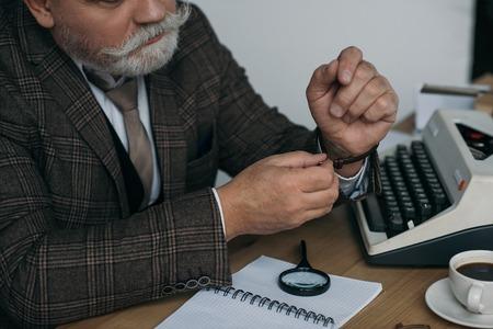 Cropped shot of senior writer putting on his vintage watch at workplace Reklamní fotografie - 112089859