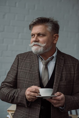 Senior man with cup of coffee in front of white brick wall background Banco de Imagens