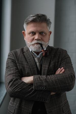 Senior man in tweed costume smoking pipe and looking at camera