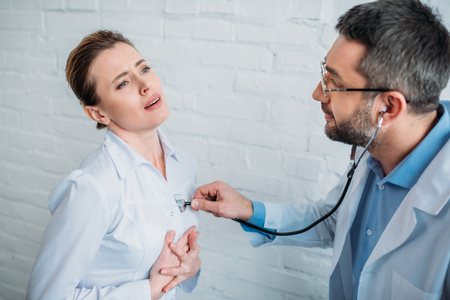 Doctor listening to heartbeat of patent with stethoscope Banque d'images - 112089914