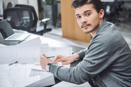 Handsome young architect drawing building plans at office and looking at camera