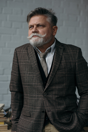 Senior man in stylish tweed suit looking away in front of white brick wall background