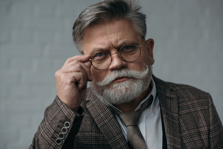 Serious senior man in tweed suit and glasses looking at camera