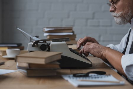 Side view of serious senior writer working with typewriter Reklamní fotografie - 112089929