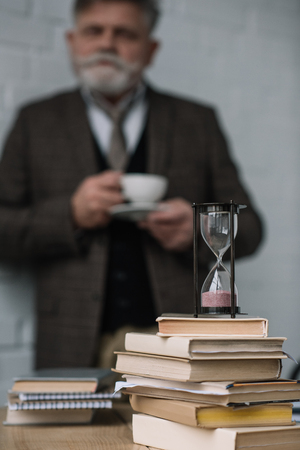 Blurred senior man drinking coffee with stack of books and hourglass on foreground Stock Photo