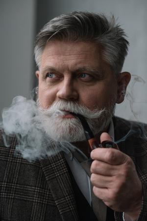 Close-up portrait of handsome senior man smoking pipe