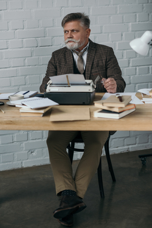 Handsome senior writer in tweed suit working with typewriter