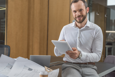 Handsome happy architect sitting on table with plans and using tablet at office Banco de Imagens