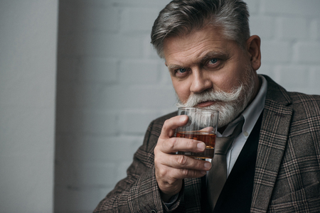 Close-up portrait of senior man in tweed suit with glass of whiskey