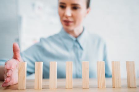 Close-up shot of attractive businesswoman assembling wooden blocks in row on worktable, dominoes effect concept