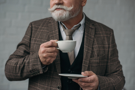 Cropped shot of senior man with cup of coffee