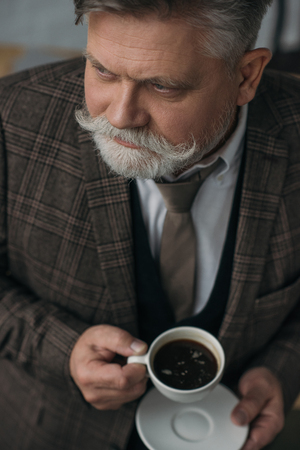 High angle view of senior man with cup of coffee Stock Photo
