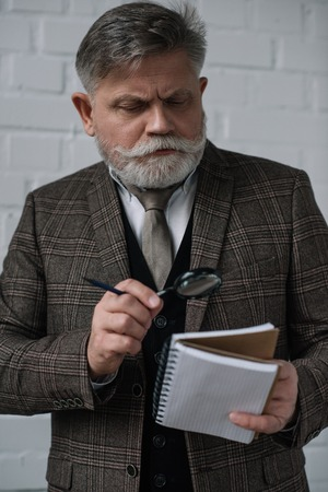 Senior man in tweed suit reading notes in notebook with magnifying glass Stock Photo