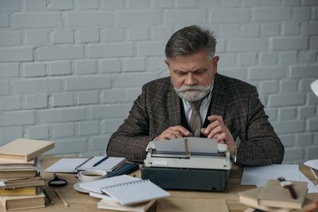 Handsome senior writer in tweed suit working with typewriter