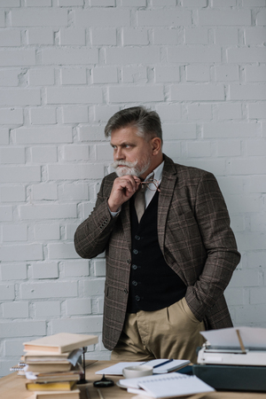 Handsome senior writer in tweed suit standing near workplace Stock Photo