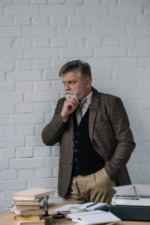 Handsome senior writer in tweed suit standing near workplace Reklamní fotografie - 112126464