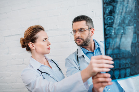 Bewildered adult doctors examining x-ray scan
