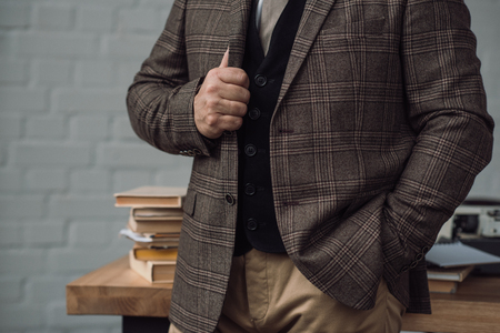 Cropped shot of senior writer in stylish tweed suit near workplace