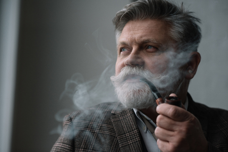 Close-up portrait of bearded senior man smoking pipe Stock Photo