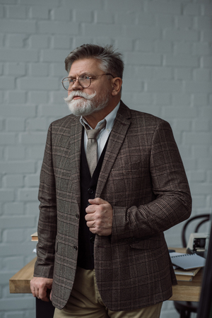 Senior writer in tweed suit and eyeglasses near workplace Stock Photo