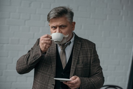 Senior man drinking coffee in front of white brick wall background