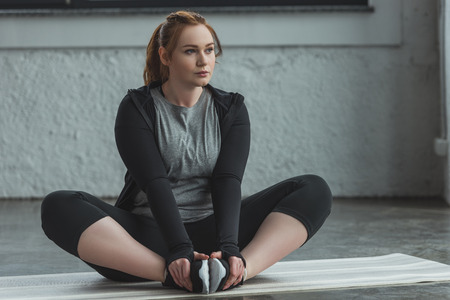 Curvy girl stretching on floor in gym Stock Photo