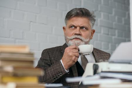 Bearded senior writer drinking coffee at workplace Reklamní fotografie - 112128157