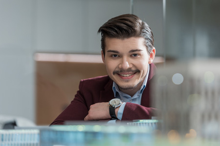 Handsome smiling architect looking at camera at office behind building models Imagens